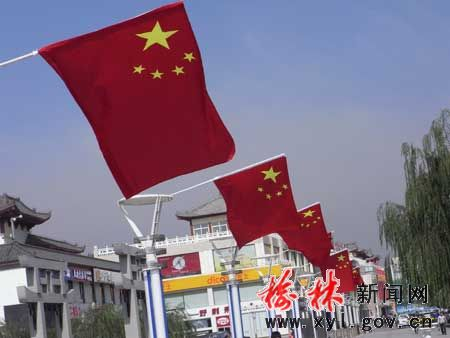 路边一面面鲜艳的五星红旗正迎着微风轻轻的摆动,映着火红的太阳,衬
